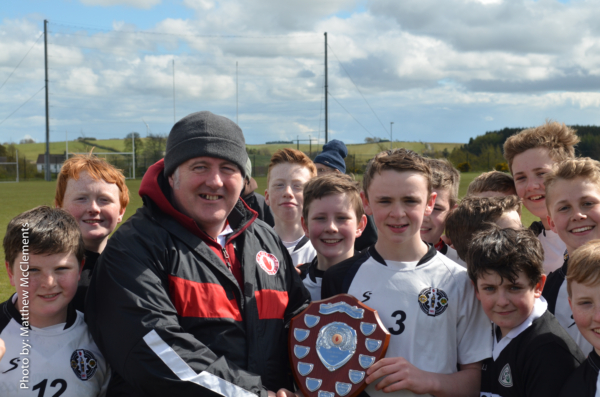 St. Enda's captain Paul Donnelly receives the Tyrone Feile shield